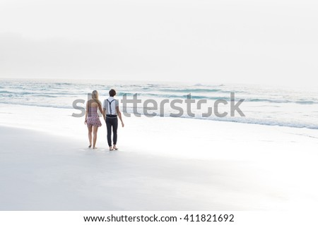 Happy romantic couple enjoying walk on the beach. Rear view of young couple holding hands and walking on white sand at beach. Newly wed couple in love relaxing on summer sunset, copy space.