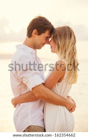Happy romantic couple having loving moment touching foreheads looking into eachothers eyes. Man and woman in love on the beach at sunset - stock photo