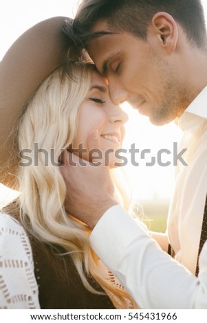 happy romantic couple hugs at sunset