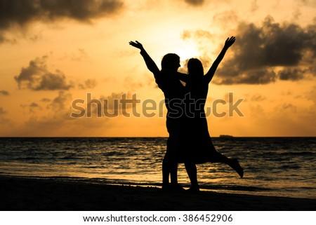 Happy romantic couple on the beach at sunset - stock photo