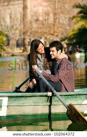 Happy romantic couple rowing a small boat on lake. - stock photo