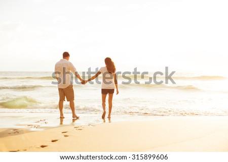 Happy Romantic Couple Walking on the Beach Enjoying the Sunset - stock photo