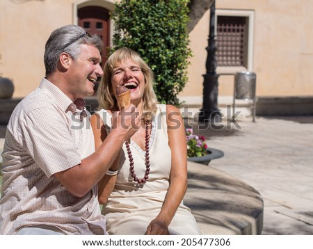 Happy romantic mature attractive middle-aged couple sitting on a stone wall in an urban square laughing at a good joke as they enjoy an ice cream in the summer heat - stock photo