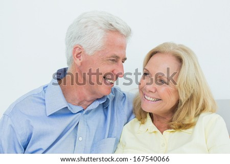 Happy romantic senior couple sitting on sofa in a house