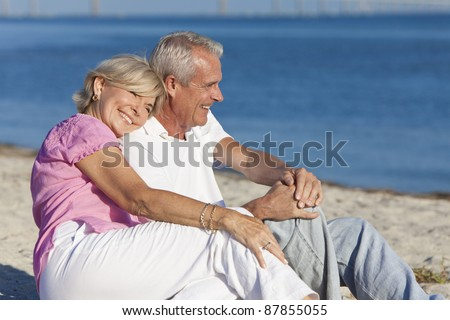 Happy romantic senior man and woman couple together on a deserted beach - stock photo