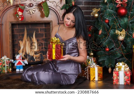 Happy romantic  woman sitting under Christmas tree with pile of Christmas presents - stock photo