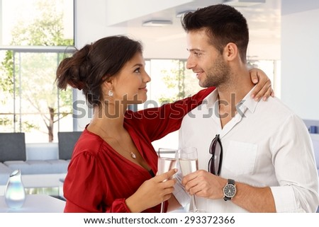 Happy romantic young casual caucasian couple with champagne at home. Attractive woman and handsome man clinking glasses. Smiling standing, embracing, eye contact. - stock photo
