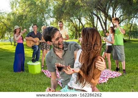 Happy romantic young teenage couple in an affectionate embrace enjoying a good laugh together in the park watched by a group of their college friends as they relax on their summer vacation - stock photo