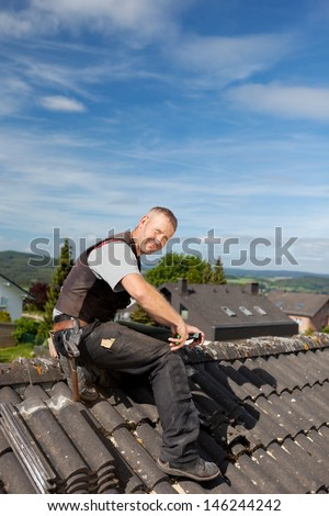 Happy roofer working on a roof tile sitting on top of a roof - stock photo