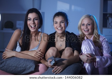 Happy roommates watching tv at home at night, wearing pyjamas, smiling happy. - stock photo