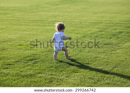Happy runaway curly barefoot little boy on summer green grass meadow sunny day outdoor, horizontal photo - stock photo