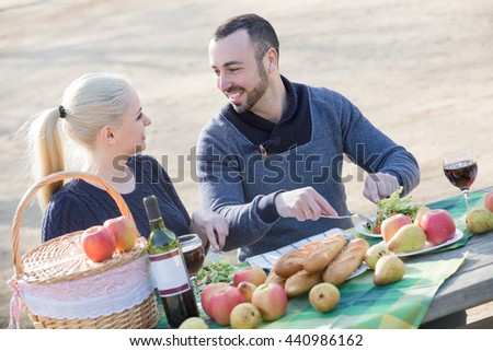 happy russian couple having picnic in sunny spring day at countryside - stock photo