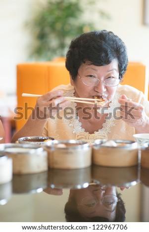 Happy 60s Senior Asian Woman dining at restaurant - stock photo