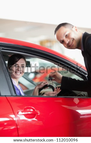 Happy salesman giving car keys to a woman in a car shop