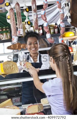 Happy Saleswoman Selling Cheese To Female Customer - stock photo