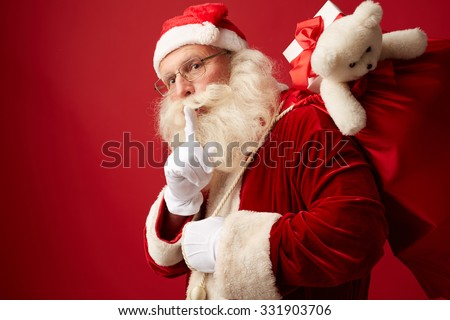 Happy Santa carrying gifts in big red sack - stock photo