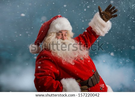 Happy Santa Claus laughing while standing outdoors at North Pole - stock photo