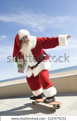 Happy Santa Claus riding skate board by the beach - stock photo