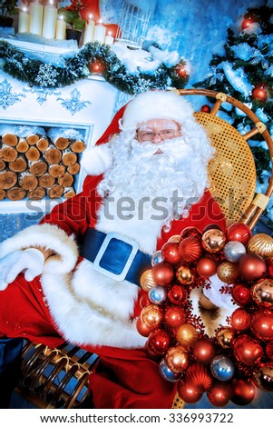 Happy Santa Claus sitting in a rocking chair with Christmas wreath in his arms. He is in the room by the fireplace and Christmas tree, beautifully decorated for Christmas. - stock photo
