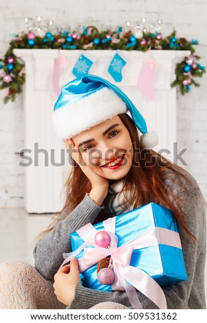Happy santa girl in santa hats with gift box near christmas firework. Holiday, x-mas or New Year celebration concept.