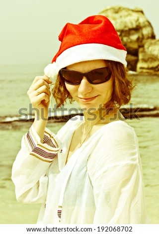 Happy Santa Girl with sunglasses on tropical beach. Beautiful brunette young woman smiling portrait in red Christmas hat celebrating New Year. Conceptual image with vintage filter - stock photo