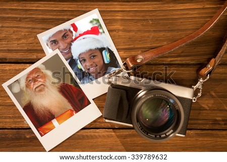Happy santa holding a glowing gift against instant photos on wooden floor - stock photo