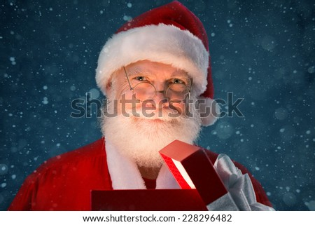 Happy Santa opening a present - stock photo