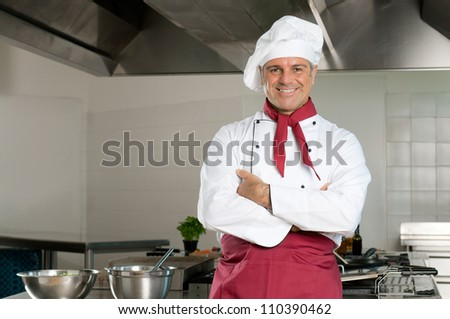 Happy satisfied chef looking at camera and smiling in his restaurant - stock photo