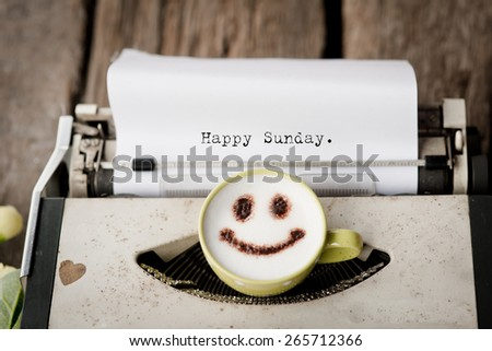 Happy Saturday on typewriter with happy face coffee cup, sepia tone. - stock photo