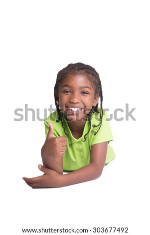 Happy school aged child  laying on the floor giving a thumbs up, isolated on white