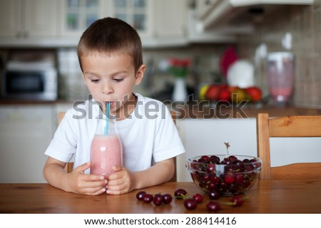Happy school boy drinking  healthy smoothie as a snack at home, cherries in a ball on the table - stock photo