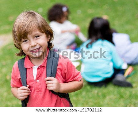 Happy school boy holding his bag and smiling  - stock photo