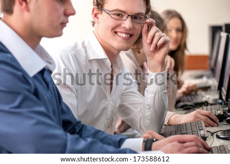 Happy school boy with glasses in schoolroom - stock photo