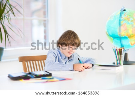 Happy school boy writing his homework at a white desk - stock photo