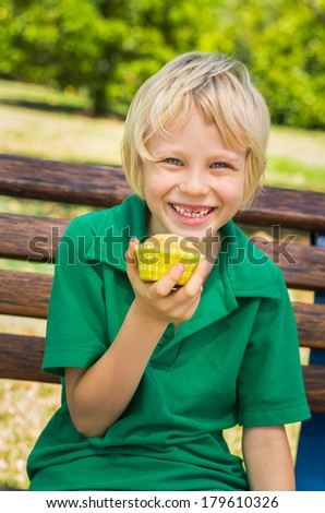 Happy school child eating homemade cupcake outdoors  - stock photo