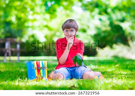 Happy school child, laughing boy sitting on a green lawn in the school yard looking through a magnifying glass exploring leaves and reading books for science class, back to school concept - stock photo