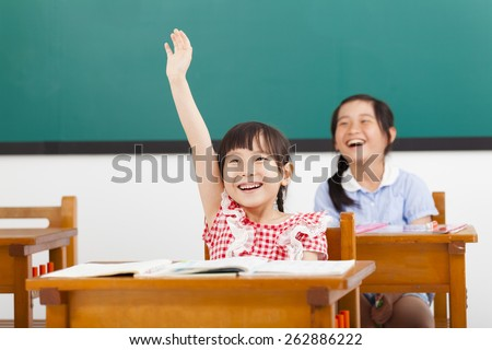 happy school children  raised hands in class - stock photo