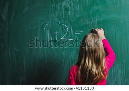 happy school girl on math classes finding solution and solving problems - stock photo