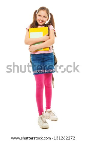 Happy school girl with books and beautiful ponytails standing holding pile of books and smiling, isolated on white, full length portrait - stock photo
