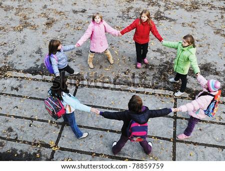 happy school girls running outdoor at sunny autumn day - stock photo