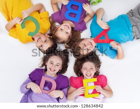 Happy school kids with colorful alphabet letters laying in circle on the floor - stock photo