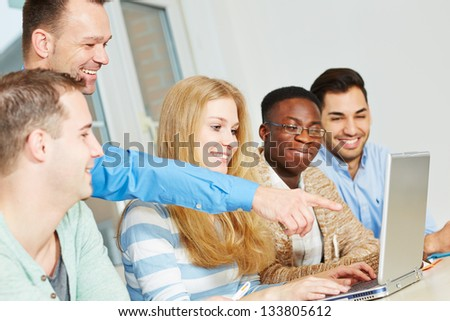 Happy school teacher pointing with his hand to laptop computer in class