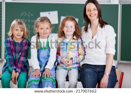 Happy school team of three pretty young girl pupils and their attractive friendly teacher posing together sitting on a table in the classroom - stock photo
