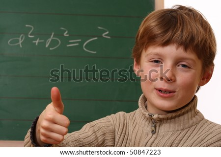 Happy schoolboy at the chalkboard