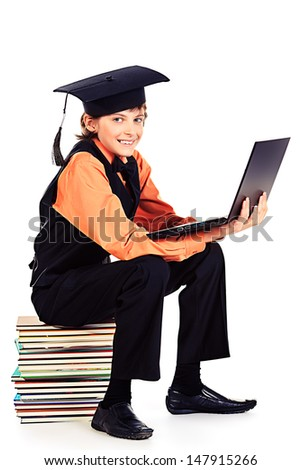 Happy schoolboy in academic hat sitting on a stack of books and holding a laptop. Isolated over white. - stock photo