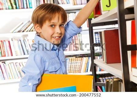 Happy schoolboy searching books in library - stock photo