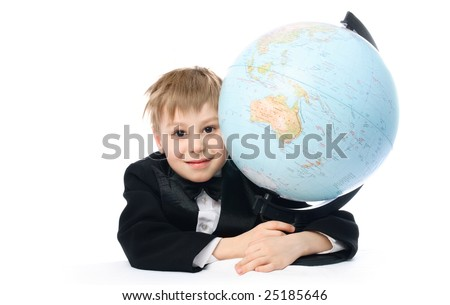 happy schoolboy sitting by the table and embracing a big globe
