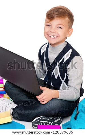 Happy schoolboy sitting on floor with books and laptop on white background - stock photo