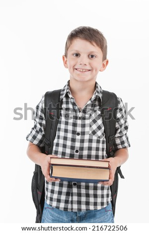 Happy schoolboy wearing backpack and holding books. cute schoolboy standing isolated on white background - stock photo