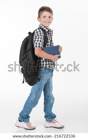 Happy schoolboy wearing backpack and holding books. cute schoolboy walking isolated on white background - stock photo